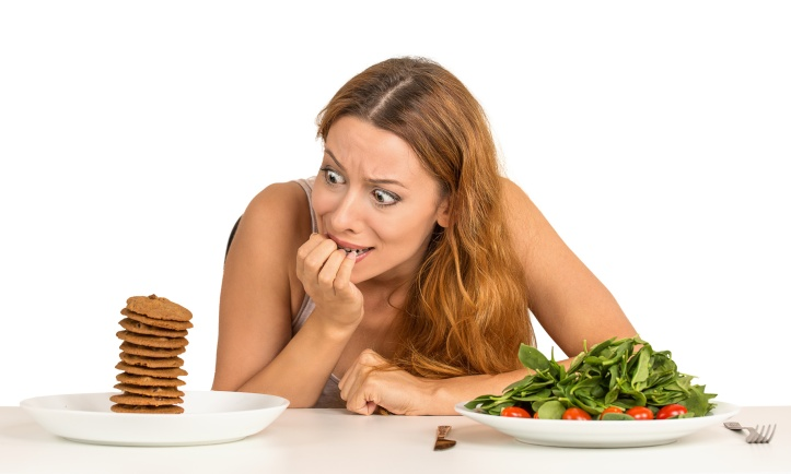 woman deciding whether to eat healthy food or sweet cookies