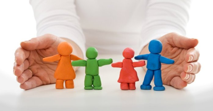 Clay people family protected by woman hands - life insurance concept